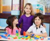 Menina com os amigos que jogam blocos na sala de aula Fotografia de Stock