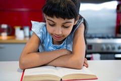 Menina com os braços cruzados lendo a novela em casa foto de stock royalty free