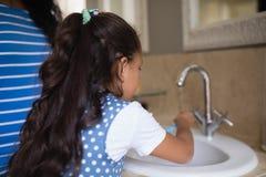 Menina com os dentes de escovadela da mãe no dissipador do banheiro fotografia de stock