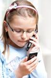 Menina com os dois telefones móveis fotografia de stock