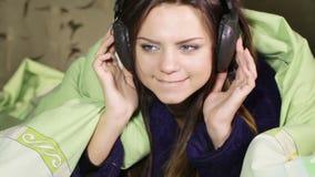 Menina com os fones de ouvido na casa da cama vídeos de arquivo