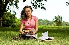A menina com os livros que sentam-se em uma grama Foto de Stock Royalty Free