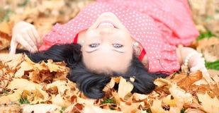 menina com os olhos azuis que encontram-se nas folhas de outono Fotografia de Stock Royalty Free