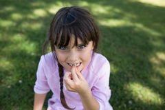 Menina com os olhos azuis que sentam-se na grama fotos de stock