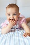 Menina com os olhos cinzentos que encontram-se em uma cama foto de stock