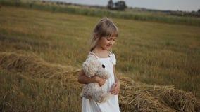 A menina com os olhos escuros bonitos anda o campo após a chuva e é jogada por um urso do brinquedo filme