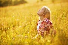 Menina com os olhos fechados nos wildflowers Fotografia de Stock Royalty Free