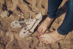 Menina com os pés descalços nas calças de brim na areia com com os pés descalços Fotografia de Stock Royalty Free