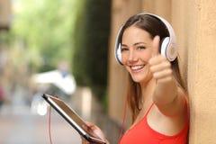 Menina com os polegares que usam acima uma tabuleta com fones de ouvido Fotos de Stock