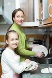 Menina com os pratos de lavagem da mãe fotos de stock