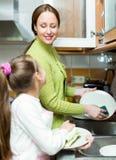 Menina com os pratos de lavagem da mãe foto de stock