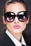 Menina com os vidros de sol grandes que emitem o beijo Fotografia de Stock Royalty Free