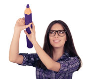 Menina com os vidros que guardam o lápis roxo gigante Fotografia de Stock