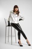 Menina com pés muito longos nas calças de couro imagem de stock