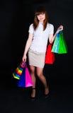 A menina com pacotes de papel multi-colored Fotografia de Stock Royalty Free
