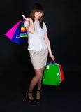A menina com pacotes de papel multi-colored Foto de Stock