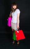 A menina com pacotes de papel multi-colored Fotos de Stock