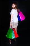 A menina com pacotes de papel multi-colored Imagem de Stock