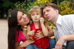 A menina com pais, começa acima bolhas de sabão Fotografia de Stock
