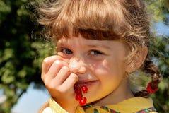 Menina com passas de Corinto vermelhas Fotografia de Stock Royalty Free