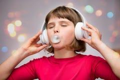 Menina com pastilha elástica dos fones de ouvido no branco foto de stock