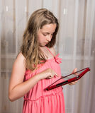 Menina com PC da tabuleta em casa Foto de Stock