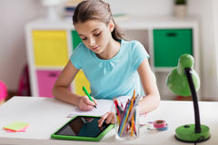 Menina com PC da tabuleta que escreve ao caderno em casa Fotos de Stock Royalty Free