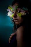 Menina com a pena colorida em sua face Fotos de Stock Royalty Free