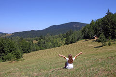 A menina com polegares acima está sentando-se no prado Foto de Stock Royalty Free