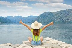Menina com polegares acima na baía de Kotor das férias de verão Imagens de Stock Royalty Free
