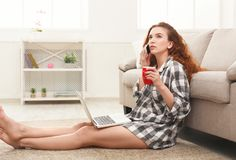 Menina com portátil e assento móvel no assoalho Fotos de Stock Royalty Free