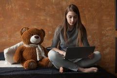 Menina com portátil e brinquedo Imagem de Stock Royalty Free