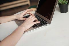 Menina com portátil que datilografa e que pensa Imagem de Stock