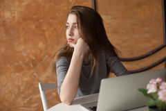 Menina com portátil que datilografa e que pensa Fotos de Stock