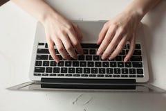 Menina com portátil que datilografa e que pensa Imagem de Stock Royalty Free