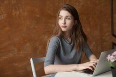Menina com portátil que datilografa e que pensa Fotos de Stock Royalty Free