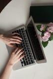 Menina com portátil que datilografa e que pensa Fotografia de Stock