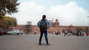 Menina com posição da trouxa contra o destino famoso do turista do forte vermelho histórico antigo do monumento na Índia Ásia w d filme