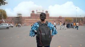 Menina com posição da trouxa contra o destino famoso do turista do forte vermelho histórico antigo do monumento no cl de Ásia da  filme