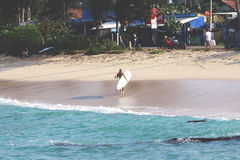 Menina com a prancha na praia fotos de stock