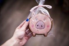 A menina com pregos azuis guarda à disposição um símbolo de 2019 - um porco pão-de-espécie cor-de-rosa sob a forma de uma papeira fotos de stock royalty free