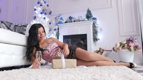 Menina com presente e champanhe perto da árvore de Natal vídeos de arquivo