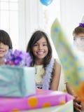 Menina com presentes de aniversário no primeiro plano Foto de Stock