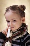 Menina com pulverizador nasal - lutando a gripe Fotos de Stock Royalty Free