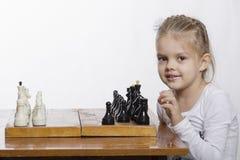 A menina com quatro anos aprende jogar a xadrez Fotos de Stock