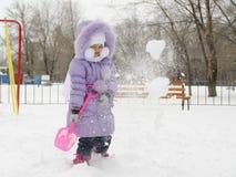 A menina com quatro anos jogou-se com pás da neve Foto de Stock
