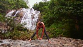 A menina com rabo de cavalo dobra-se ao pé desencapado na pose da ioga na rocha video estoque