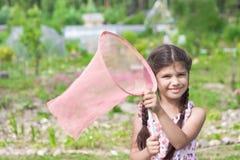 Menina com a rede da borboleta que tem o divertimento no verão Fotografia de Stock