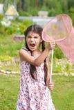 Menina com a rede da borboleta que tem o divertimento no verão Foto de Stock Royalty Free
