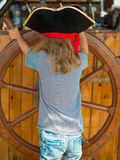 Menina com a roda do navio de madeira Fotos de Stock Royalty Free